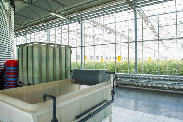Interior e equipamento com tubagens e tanque de água em estufa moderna