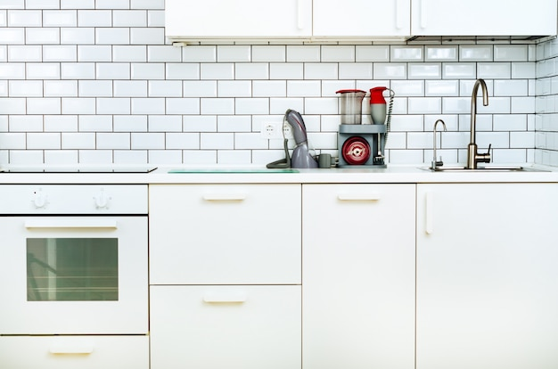 Interior e projeto minimalistic brancos da cozinha. parede de azulejos.