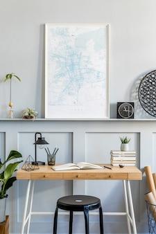 Interior elegante da sala de escritório em casa com mapa de pôster, mesa de madeira, cadeira preta, relógio, livros, plantas, cactos, material de escritório, lâmpada e acessórios pessoais em decoração moderna.