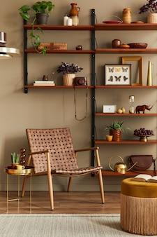 Interior elegante da sala de estar com poltrona de vime, estante de madeira, plantas, pufe, moldura, tapete, decoração e acessórios elegantes na decoração da casa.