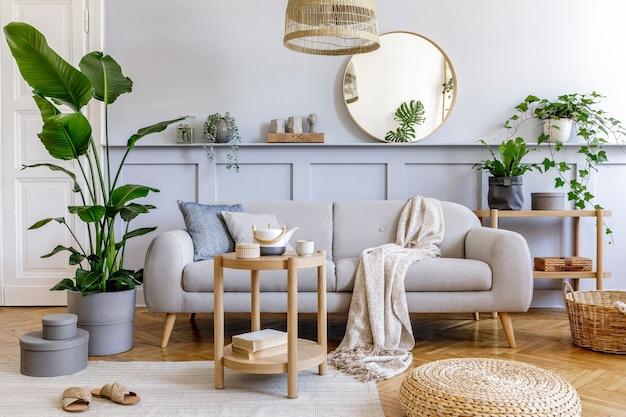 Interior elegante da sala de estar com sofá cinza de design, mesa de café, pufe de rattan, cesta, prateleira, espelho, plantas tropicais, decoração, carpete e acessórios pessoais elegantes em decoração moderna.