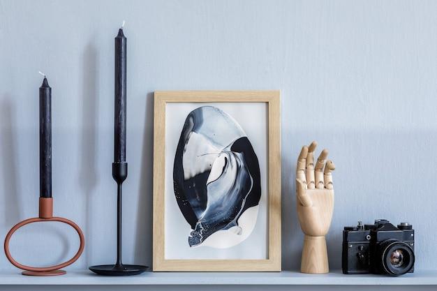 Interior elegante da sala de estar em um apartamento elegante com moldura simulada, castiçal, câmera fotográfica, painéis de madeira cinza e acessórios elegantes na prateleira em um cenário doméstico moderno.