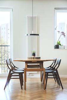 Interior elegante de sala de jantar escandinava com mesa de design familiar, cadeiras e acessórios