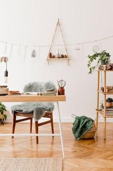Interior elegante do espaço de escritório em casa com mesa de madeira, acessórios florestais, planta de abacate, prateleira de bambu, plantas e decoração de vime. decoração neutra.