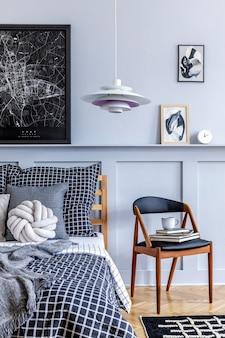 Interior elegante do quarto moderno com cadeira de design, molduras, livro, relógio, decoração, carpete, lindos lençóis, cobertor e travesseiros na decoração moderna da casa.