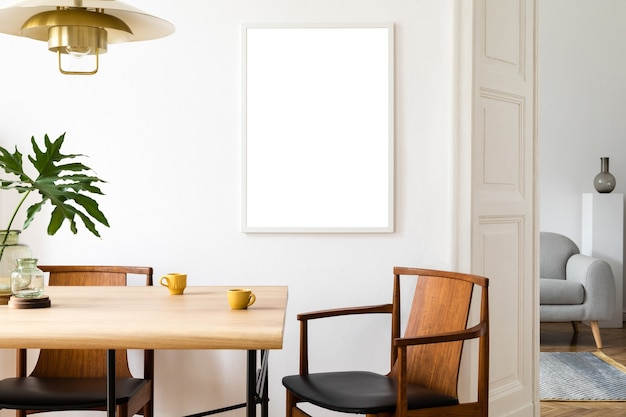 Interior elegante e eclético da sala de jantar com mapa de pôster simulado, cadeiras de design de mesa compartilhadas, lâmpada pedante de ouro e sofá elegante no segundo espaço. paredes brancas, parquete de madeira. folhas tropicais em um vaso.