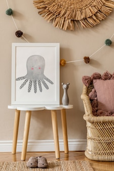 Interior elegante e moderno de bebê recém-nascido escandinavo com moldura em cima da mesa. brinquedos, sofá com almofada e bolas coloridas de algodão penduradas. parede bege. projetar a encenação em casa.
