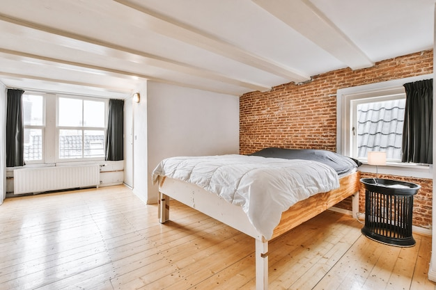 Interior elegante e simples do quarto com parede de tijolos e cama de madeira sob o teto branco com vigas
