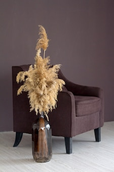 Interior elegante escandinavo aconchegante em estilo minimalista, decoração moderna, poltrona, vaso com buquê de grama dos pampas