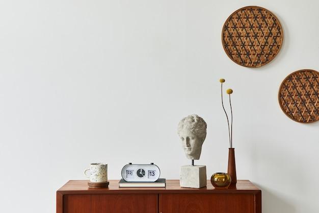 Interior escandinavo com design elegante de cômoda de teca decoração de vime na parede relógio com flores secas e acessórios pessoais elegantes sala de estar neutra em casa clássica espaço de cópia