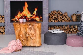 Interior escandinavo com uma lareira, mesa de coto, uma pilha de toras para fogo
