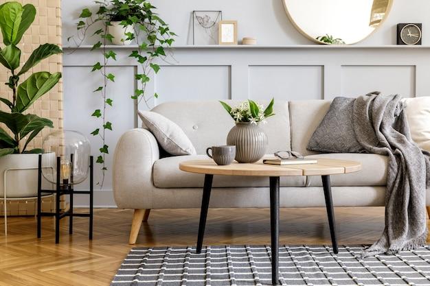Interior escandinavo da sala de estar com sofá cinza de design, mesa de centro de madeira, plantas tropicais, prateleira, espelho, móveis, travesseiro xadrez, bule, livro e acessórios pessoais elegantes na decoração da casa.