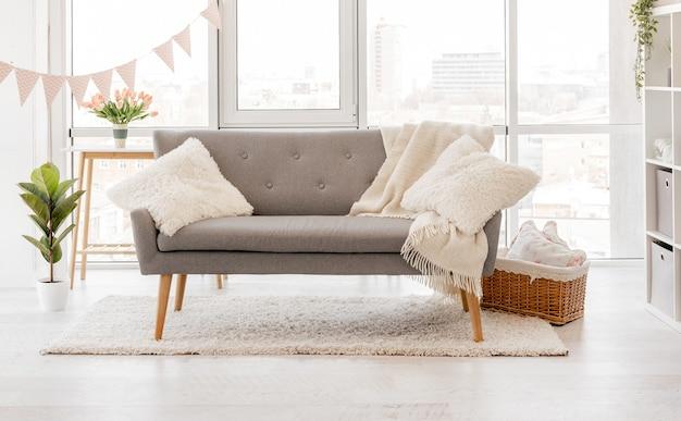 Interior escandinavo da sala de estar com sofá cinza e janelas panorâmicas