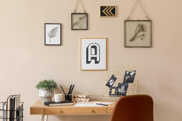 Interior escandinavo elegante de escritório doméstico com muitas molduras para fotos, mesa de madeira, cadeira marrom, plantas, escritório e acessórios pessoais. encenação em casa neutra moderna.