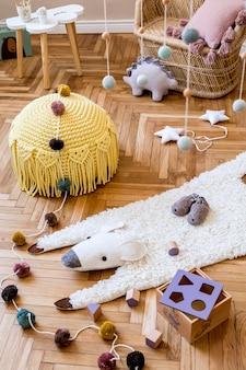 Interior escandinavo elegante de quarto infantil com móveis de design, brinquedos naturais, bandeiras coloridas penduradas, animal de pelúcia, acessórios infantis, tapete de animais e ursinhos de pelúcia. decoração moderna neutra.