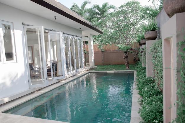Interior escandinavo minimalista com portas de vidro abertas para a piscina e plantas tropicais. conceito de relaxamento