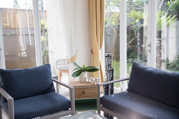Interior escandinavo minimalista com sofá de design, plantas tropicais, mesa de centro, placa de amor e velas. interior de estilo bali