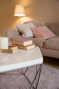 Interior escandinavo. parede marrom na sala de estar aconchegante. quarto confortável. almofadas rosa e cinza no sofá. lâmpada, livros e velas na mesa. copie o espaço. dia mundial do livro