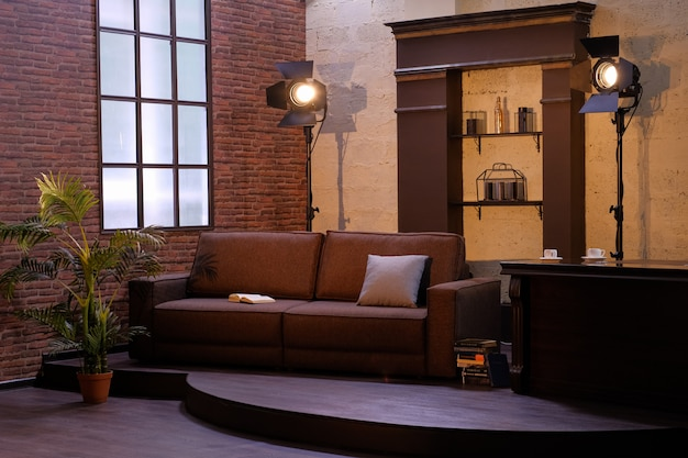 Interior escuro da sala com janela, sofá, planta e lâmpadas.