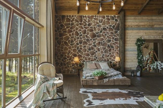 Interior escuro e aconchegante de uma grande casa de madeira, móveis de madeira e peles de animais. janela panorâmica enorme e teto muito alto.