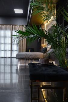 Interior escuro e elegante de apartamento masculino com iluminação, paredes decorativas, lareira, área de vestir e janela enorme