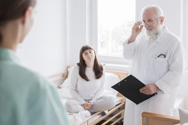 Interior espartano do quarto do hospital em que o médico e os pacientes nas camas estão localizados