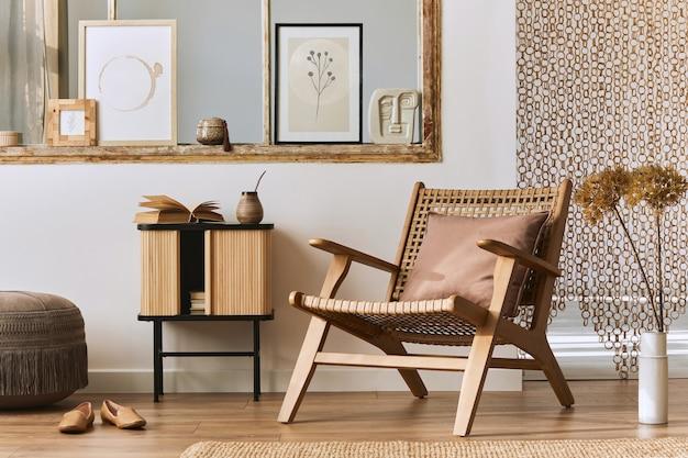 Interior exclusivo da sala de estar com poltrona de vime elegante, móveis de design, flores secas, molduras, piso de madeira, decoração e acessórios pessoais elegantes. casa moderna ..