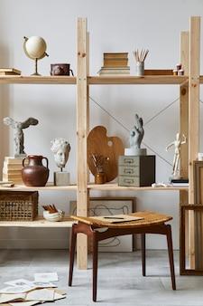 Interior exclusivo do espaço de trabalho do artista com banquinho elegante, estante de madeira, obras de arte, acessórios de pintura, decoração e objetos pessoais elegantes. sala de trabalho moderna para artista.