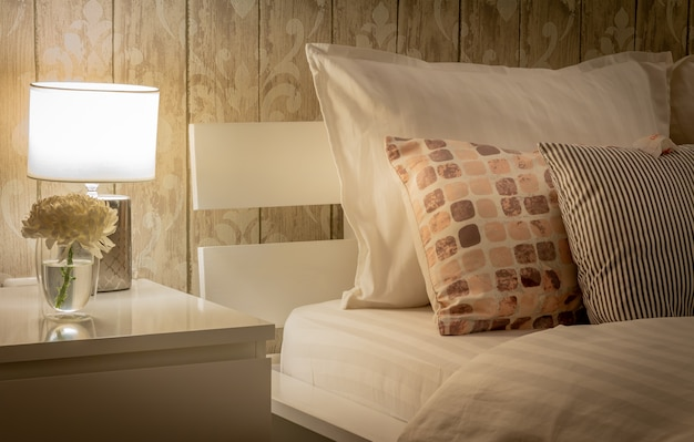 Interior home vintage com configuração de quarto, incluindo mesa de cabeceira com lâmpada. esquema de cores cinza. roupa de cama acetinada