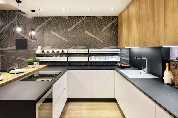 Interior longo e estreito da cozinha equipada com eletrodomésticos embutidos e armários frontais brancos iluminados