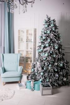 Interior luminoso com sofá, poltrona e árvore de natal