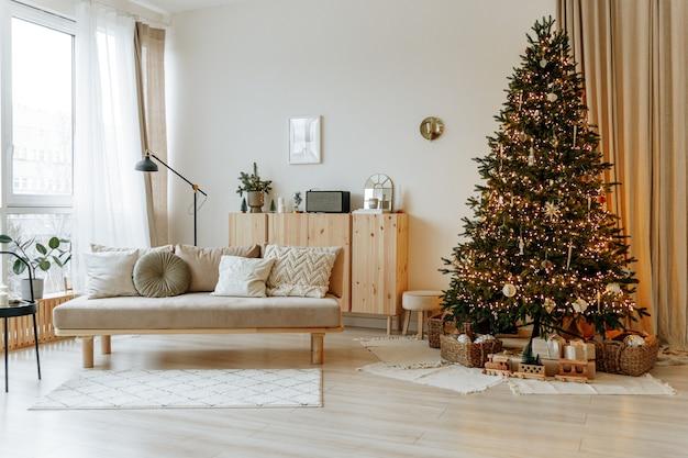 Interior luminoso da sala de estar com um sofá e uma grande árvore de natal