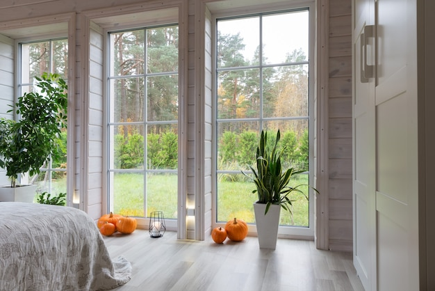 Interior luminoso da sala em uma casa de madeira com uma grande janela com vista para o pátio de outono. paisagem de outono dourada na janela branca. casa e jardim, conceito de queda.