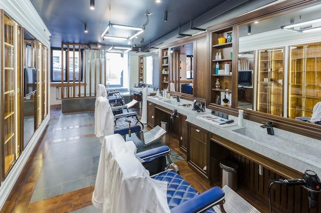 Interior luxuoso da barbearia, móveis caros azuis, acabamento em madeira, teto preto moderno