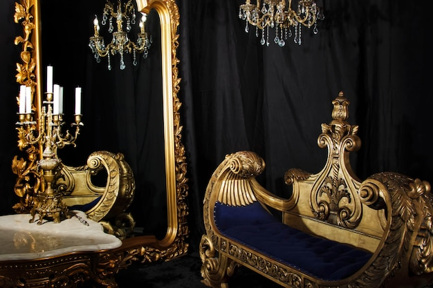 Interior luxuoso do quarto do vintage em preto e dourado. sala com espelho, sofá e candelabro