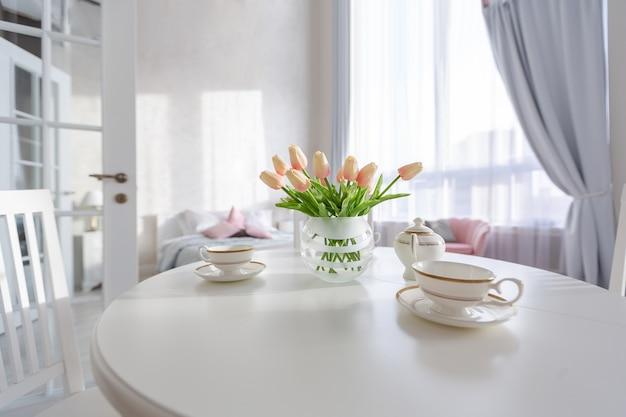 Interior luxuoso e caro de um apartamento de plano aberto em cores claras. quarto moderno e elegante com design minimalista, área para refeições e espaço para hóspedes.