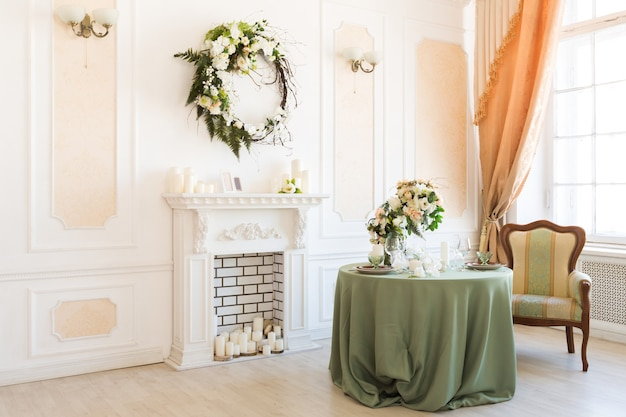Interior luxuoso e elegante de luz brilhante da sala de estar. paredes brancas decoradas com ornamentos. lareira. ninguém dentro da sala