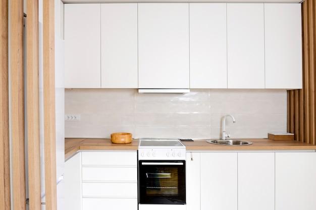 Interior luxuoso e moderno da cozinha na cor branca com elementos de madeira