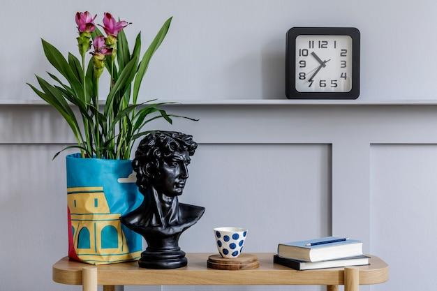 Interior minimalista da sala de estar com console de madeira, lindas plantas em vaso moderno, folha, livro, relógio, prateleira, decoração, parede cinza e acessórios pessoais em uma decoração elegante.