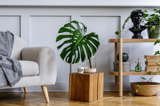 Interior minimalista da sala de estar com console de madeira, sofá, lindas plantas, folha tropical, livro, cubo, estante, decoração, parede cinza e acessórios pessoais em uma decoração elegante.