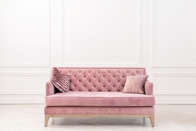 Interior minimalista da sala de visitas moderna com o sofá cor-de-rosa perto da parede branca vazia.
