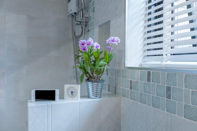 Interior moderno banheiro com telefone móvel e despertador em tempo de manhã.