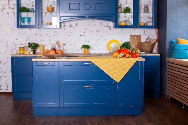 Interior moderno cozinha azul em estilo loft com móveis. cozinha escandinava elegante em decoração. cozinha de madeira em estilo rústico. mesa de madeira vazia e decoração amarela primavera no interior da cozinha.
