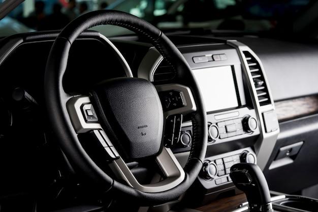 Interior moderno da caminhonete, painel de tela sensível ao toque, assentos de couro e alavanca de transmissão automática - luz negra