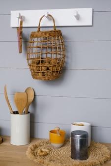 Interior moderno da cozinha com painéis de madeira cinza de estilo escandinavo na parede, nozes na cesta, louças e utensílios de cozinha