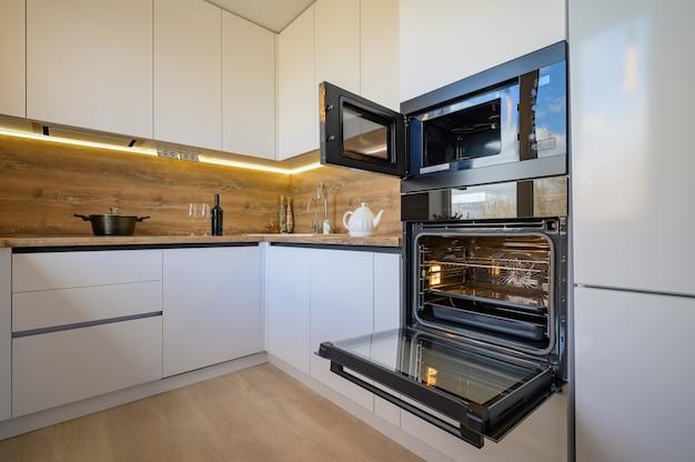 Interior moderno da cozinha de madeira branca e bege com forno aberto
