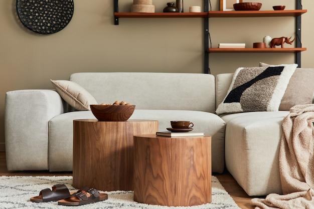 Interior moderno da sala de estar com sofá bege modular de design, mesa de centro, móveis, luminária pendente, prateleira, chinelos, carpete, decoração e acessórios pessoais elegantes na decoração da casa. modelo.