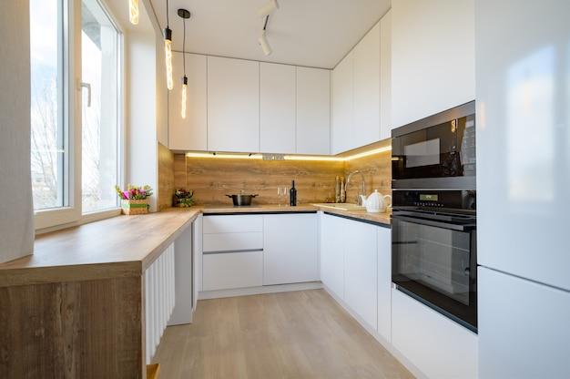 Interior moderno de cozinha de madeira branca e bege