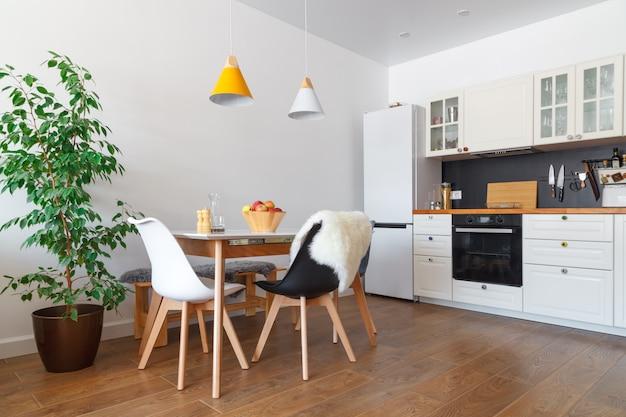 Interior moderno de cozinha, parede branca, cadeiras de madeira, flor verde em pote