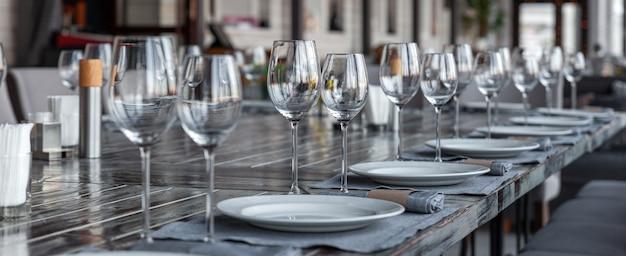 Interior moderno de restaurante com varanda, ambiente de banquete, copos, pratos